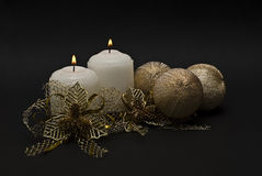 Two candles and golden bonds and balls. Royalty Free Stock Image