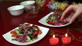 Two candles. Happy New Year. Christmas. Two servings of Thai salad. Warm salad with beef and vegetables. happy New Year. Christmas stock video