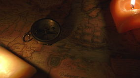 Two candles lit near the map and the compass stock footage