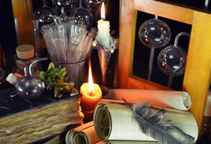 Two candles with magic bottles and books. Two candles with vintage bottles, glassware, scrolls and ancient books in witch or alchemy laboratory. Halloween or royalty free stock images