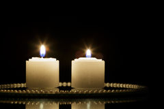Two Candles on mirror plate Stock Photos