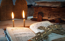 Two candles and an old metal cross on the ancient book Royalty Free Stock Photos