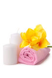 Two candles, pink towel and yellow flower. spa composition Royalty Free Stock Image