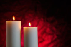 Two candles with red background. Two candles lit with red background Stock Images