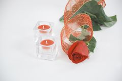 Two candles and a red rose on a white background.photo with copy Royalty Free Stock Images