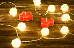 Two candles in shape of heart among the glowing lanterns made of rattan on a wooden background. Side view, closeup Stock Photography