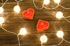 Two candles shape of heart among the glowing lanterns made of rattan on a wooden background. View from above Stock Photo