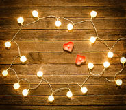 Two candles in the shape of heart among the glowing lanterns made of rattan on a wooden background. View from above Royalty Free Stock Photography