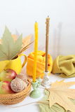 Two candles. Two thin candles, autumn leaves, apples and fabric Royalty Free Stock Image