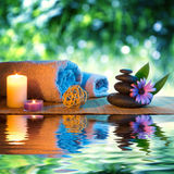 Two candles and towels black stones and purple daisy on water. For massage Stock Images