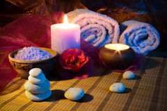 Two candles towels camellias stones and salt. For massage stock photography