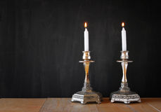Two candlesticks with burning candels over wooden table and blackboard background.  stock photo