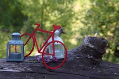Two candlesticks and a red bicycle mock-up on an old wooden log against the bokeh background of green forest. stock photos