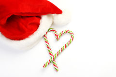 Two Candy Canes in Heart Shape and Santa Claus hat on White Background Royalty Free Stock Images