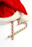 Two Candy Canes in Heart Shape and Santa Claus hat on White Background Stock Image
