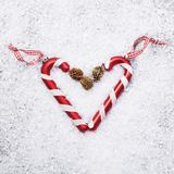 Two candy canes heart on snow background Stock Image
