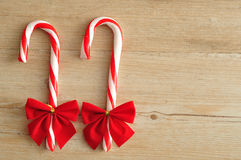 Two candy canes with red bows isolated. On a wooden background Royalty Free Stock Image