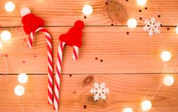 Two candy canes in red hats on wooden background royalty free stock photography