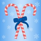 Two Candy Canes With Ribbon. Two Christmas candy canes crossed with blue ribbon bow and snowflakes on blue background Royalty Free Illustration