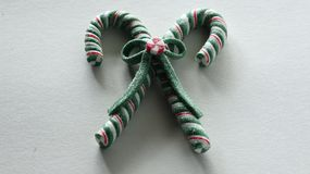 Two candy canes tied together with a bow on a white festive background royalty free stock photo