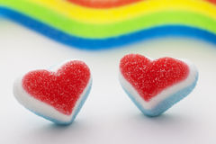 Two candy hearts with a rainbow flag. Two candy hearts with a blurred rainbow flag in the background Stock Image