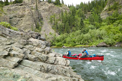 Two canoeists navigating rocks in turbulent river. Two canoeists navigate rocks and shallow water during an adventure on a turbulent river in the Alaskan Stock Image