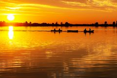 Two canoes pulled by a motorboat during beautiful sunset in lake Zoetermeerse plas royalty free stock image