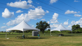 Two canopies three porta pottys and power lines. Under a sky with cumulus clouds royalty free stock photography