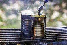 Two cans of food being cooked over a campfire, steam rising, spo. On held over one. Camping and survival cooking concepts Royalty Free Stock Image