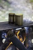 Two cans of soup being cooked over campfire on simple grill, ste. Am rising. Camping concept Stock Photos