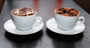 Two cappuccino coffe cup at the table.  Stock Images