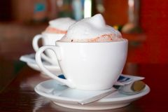 Two cappuccino cups with milk foam and cinnamon stock photo