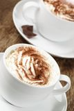 Two Cappuccinos. Two cappuccino coffees topped with fresh cream and dusted with chocolate powder Stock Photos