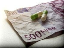 Two Capsules Of White And Green On A Ticket Used 500 Euros. Conceptual Image Stock Photos