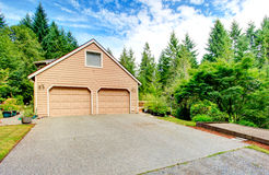 Two car garage with driveway. Beige two car garage with driveway stock photo