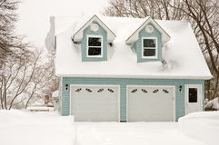 Two car garage in snowstorm. A large two car garage during a heavy winter snowstorm Royalty Free Stock Images