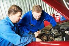 Two car mechanic diagnosing auto engine problem Royalty Free Stock Photo