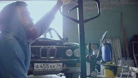 Two car mechanic prepare a trolley to transport the engine. The motor hangs on chains, from him drops of liquid fall to the floor of the garage stock footage