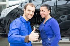 Two mechatronic technicians in garage with thumbs up Stock Photo