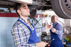 Two car mechanics at workshop. Two car mechanics checking up pressure in tires at workshop Stock Photos