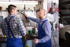 Two car mechanics at workshop. Portrait of two professional car mechanics working together at garage Stock Photos