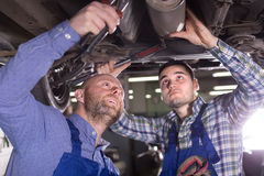 Two car mechanics at workshop. Portrait of two serious professional car mechanics at garage Royalty Free Stock Image