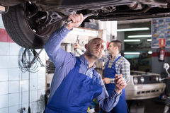 Two car mechanics at workshop. Portrait of two serious professional car mechanics working at garage Royalty Free Stock Image