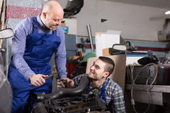 Two car mechanics at workshop. Portrait of two smiling professional car mechanics working together at garage Royalty Free Stock Image
