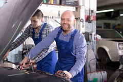 Two car mechanics at workshop Stock Photography