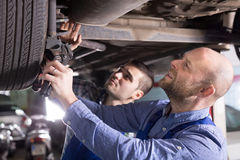 Two car mechanics at workshop. Two professional car mechanics checking up pressure in tires at garage Stock Photos
