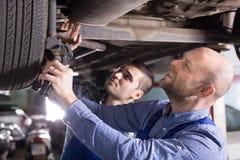 Two car mechanics at workshop Stock Photos
