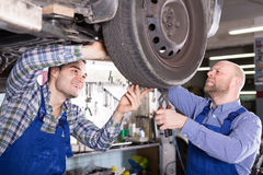 Two car mechanics at workshop. Two professional car mechanics checking up pressure in tires at garage and smiling Royalty Free Stock Images