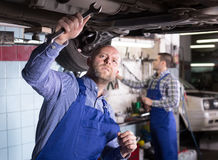 Two car mechanics at workshop. Two professional serious car mechanics repairing car at garage Stock Photography