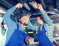 Two car mechanics at workshop. Two professional serious car mechanics working together at garage Stock Images